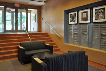 Sitting area and mailboxes in lobby, and steps leading to the parking lot in the rear of the building.