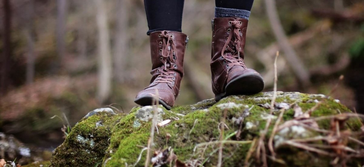 Female hiker standing on a large rock in the woods. Photo by Leah Kelley.