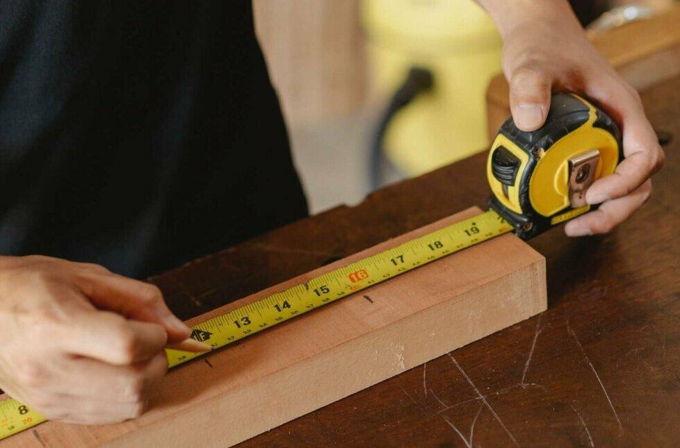 Man using a tape measure. Photo credit Ono Kosuki