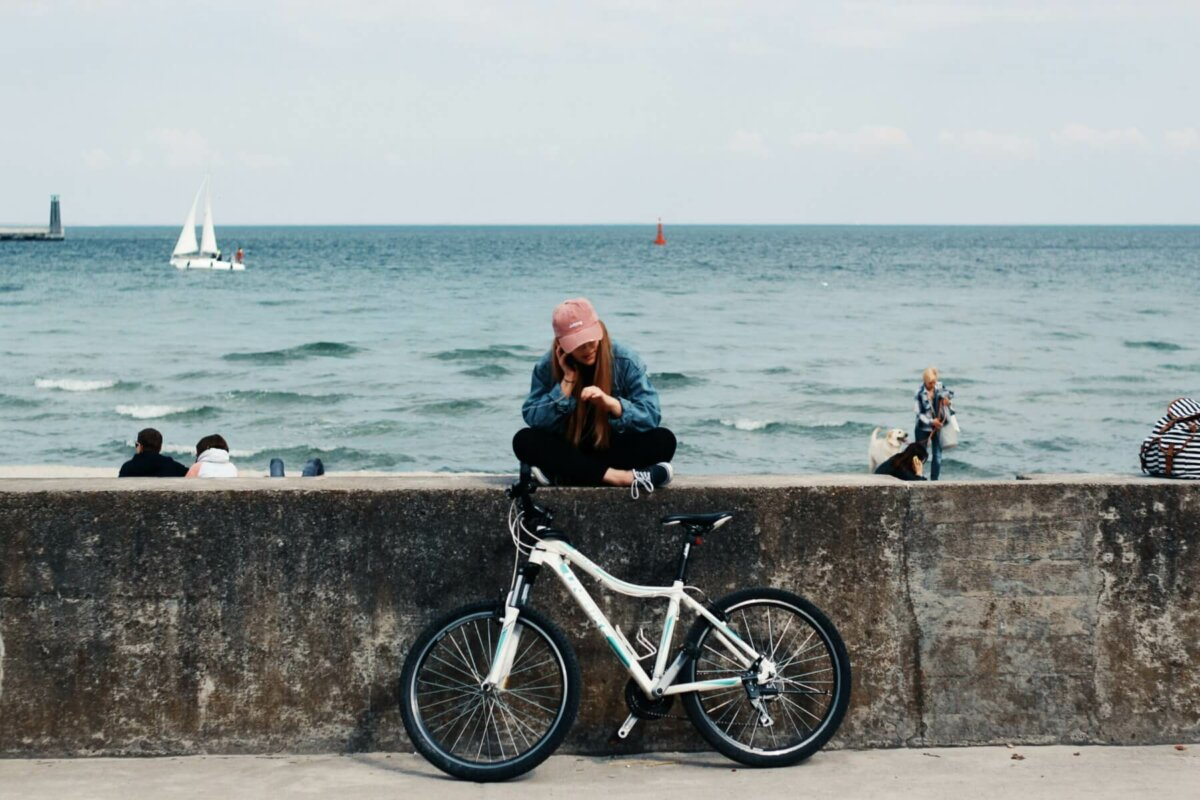 Woman sitting on pier with bicycle. Photo credit: Pawel L.