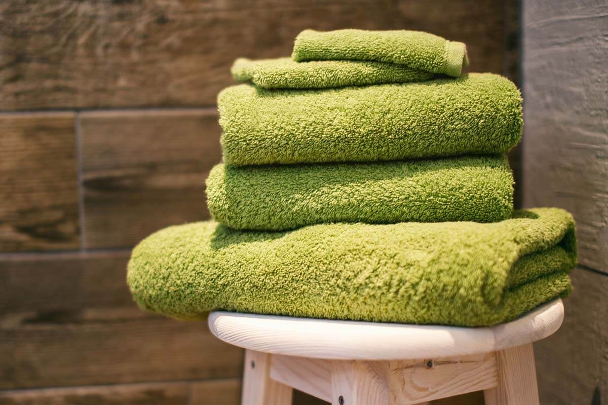 Folded towels on a wooden stool. Photo credit: Denny Muller